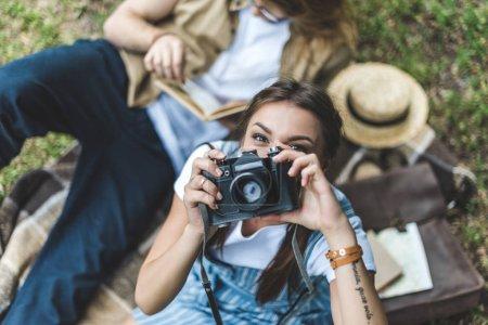 Photo pour Vue de dessus de la femme prenant des photos avec un appareil photo vintage tout en se relaxant dans le parc avec petit ami - image libre de droit