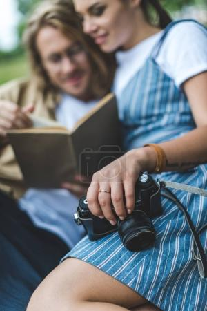 Couple reading book in park