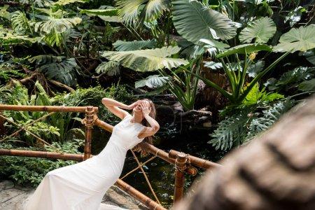 Photo pour Belle femme heureuse en robe blanche posant en orangerie tropicale - image libre de droit