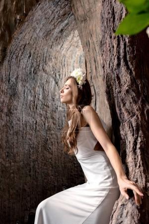 Photo pour Belle mariée sensuelle posant en robe de mariée blanche et couronne de fleurs - image libre de droit