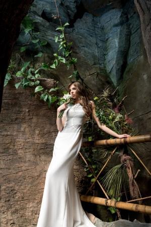 Foto de Atractiva novia sensual posando en vestido blanco con ramo de boda - Imagen libre de derechos