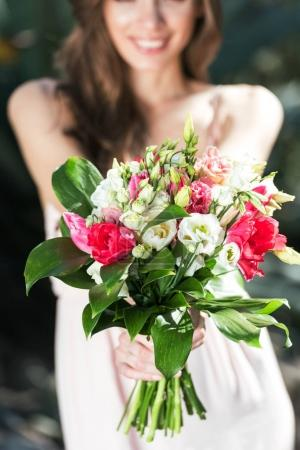 Photo for Young woman showing bouquet of flowers - Royalty Free Image