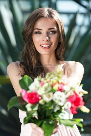 Photo for Young smiling beautiful woman showing bouquet of flowers - Royalty Free Image