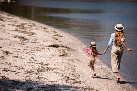 mother and daughter walking at seashore