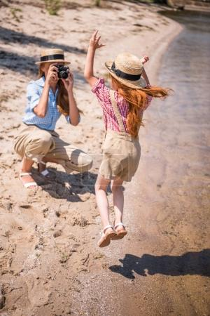 mother photographing daughter on beach