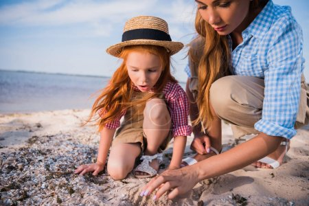 mother and daughter collecting seashells