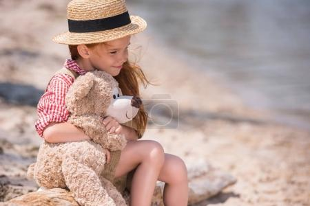 Photo for Pensive little girl hugging teddy bear and looking away while sitting on seashore - Royalty Free Image