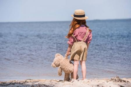 child with teddy bear at seashore