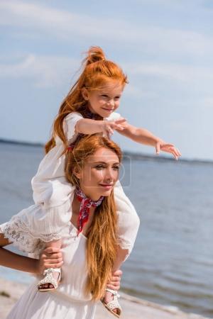 Photo pour Heureuse mère fille adorable rousse exerçant son cou tout en marchant au bord de mer - image libre de droit