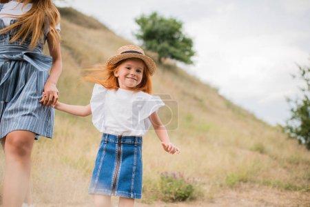 Photo pour Photo recadrée de mère et sa fille main dans la main et de marcher sur la colline herbeuse - image libre de droit