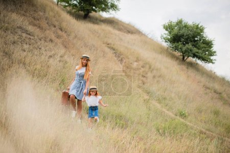 mother and daughter walking on hill