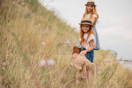 Photo for Beautiful mother and daughter with suitcase and teddy bear holding hands while walking together on grassland - Royalty Free Image