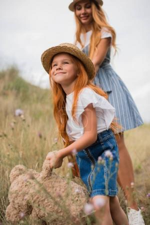 Photo for Happy mother and daughter with suitcase and teddy bear walking together in grass - Royalty Free Image