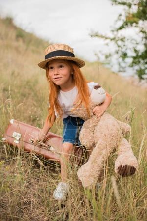 Photo pour Jolie fille aux cheveux rouge tenant l'ours en peluche et valise tout en regardant loin à l'extérieur - image libre de droit