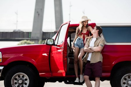 Photo pour Heureux jeune couple avec voiture classique regardant les uns les autres - image libre de droit
