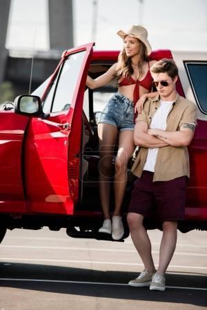 Photo pour Beau jeune couple avec voiture classique - image libre de droit