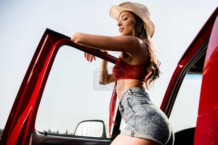 woman posing next to car