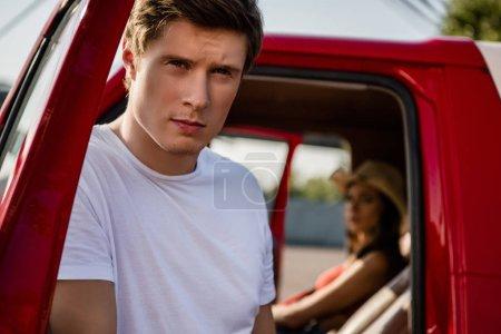 Photo pour Bel homme posant près de la voiture avec belle jeune femme à l'intérieur - image libre de droit