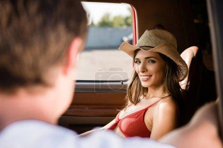 Photo pour Belle jeune femme souriant à l'homme dans la fenêtre de la voiture - image libre de droit