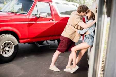 Photo pour Attrayant jeune couple embrasser à côté de vintage voiture rouge - image libre de droit