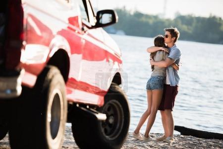 Couple hugging near car