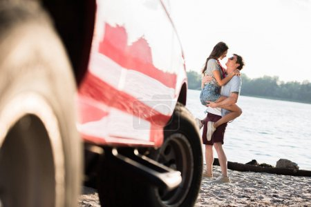 Photo for Close-up view of red car and sensual young couple hugging at riverside - Royalty Free Image