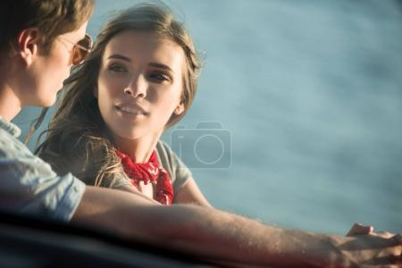 Photo for Beautiful young couple looking at each other, view through the car window - Royalty Free Image