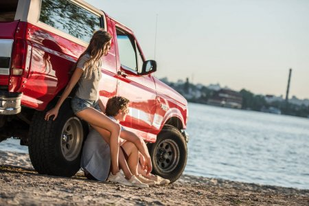 Photo for Beautiful young couple leaning on red car and looking away at riverside - Royalty Free Image