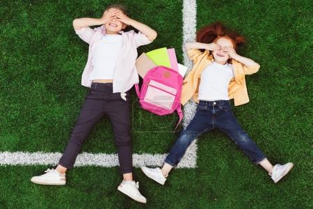 Photo for Top view of cute smiling schoolgirls closing eyes while lying together on grass - Royalty Free Image