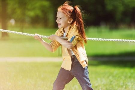 Photo for Adorable happy redhead girl playing tug of war in park - Royalty Free Image
