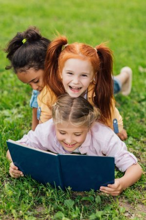 multiethnic kids reading book on grass