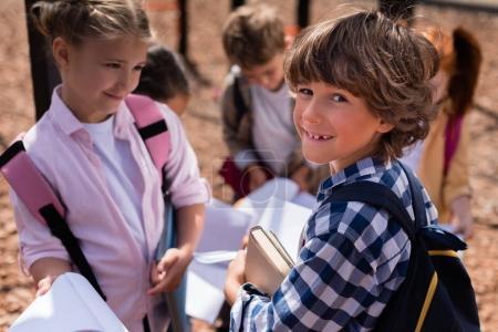 Foto de Lindo feliz escolares sosteniendo libros y sonriendo a cámara en patio - Imagen libre de derechos
