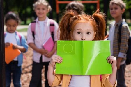 redhead child holding book