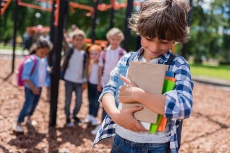 Photo pour Mignon sourire petit garçon tenant des livres tandis que des amis debout derrière sur aire de jeux - image libre de droit
