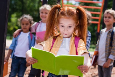 child with book on playground