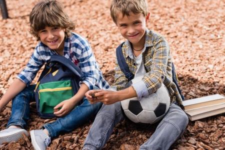 Photo pour Adorables garçons heureux avec ballon de football et des livres souriant à la caméra - image libre de droit