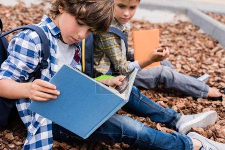 Foto de Lindos poco colegiales leer libros mientras estaba sentado al aire libre - Imagen libre de derechos