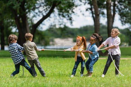 Photo for Side view of beautiful little multiethnic kids playing tug of war in park - Royalty Free Image