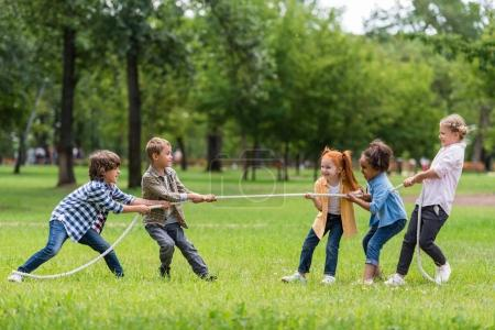 Photo for Side view of cute little multiethnic children pulling rope in park - Royalty Free Image