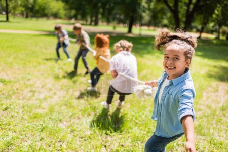 Photo for Happy multiethnic kids playing tug of war in park - Royalty Free Image