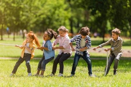 Photo for Side view of adorable multiethnic kids pulling rope in park - Royalty Free Image