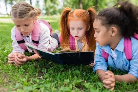 Multiethnic kids reading book on grass