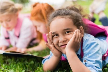 Photo pour Adorable afro-américaine fille souriant à la caméra tout en étant couché avec des amis sur l'herbe - image libre de droit