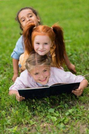 Multiethnic schoolgirls reading book