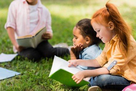 Photo pour Belles filles multiethniques lisant des livres ensemble dans le parc - image libre de droit