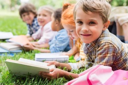 Photo pour Adorables petits enfants lisant des livres tout en étant allongé sur l'herbe dans le parc - image libre de droit