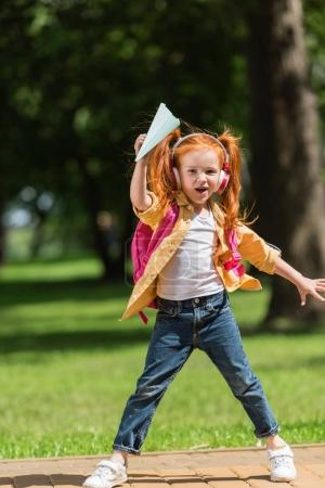 Photo for Adorable red haired girl in headphones holding paper plane and looking at camera - Royalty Free Image