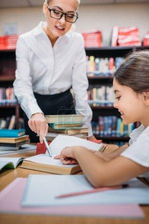 enseignant aider écolière avec des devoirs