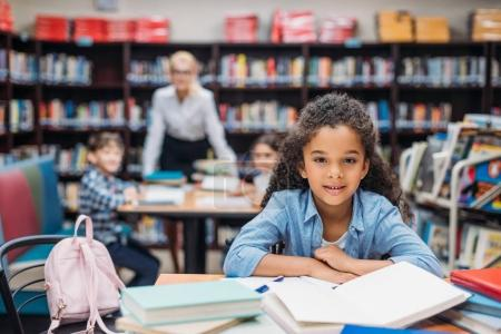 Photo for Beautiful african american schoolgirl with pile of books at library - Royalty Free Image