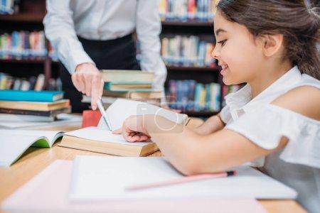 Teacher helping schoolgirl with homework